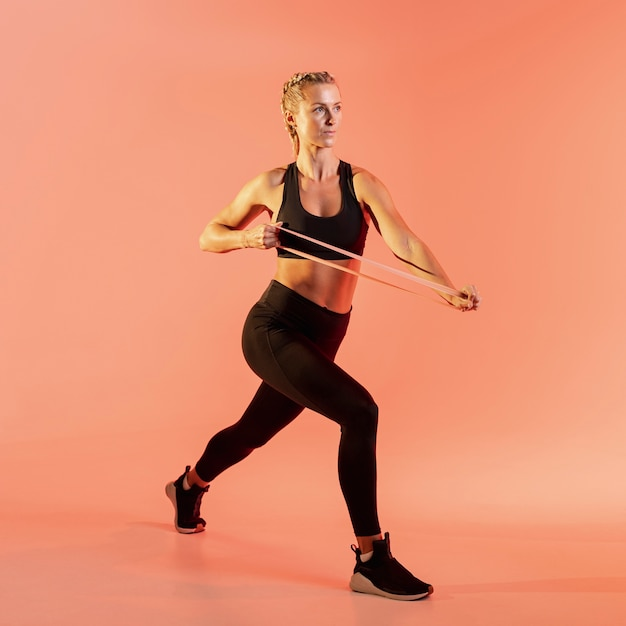 Front view woman training with elastic band Free Photo