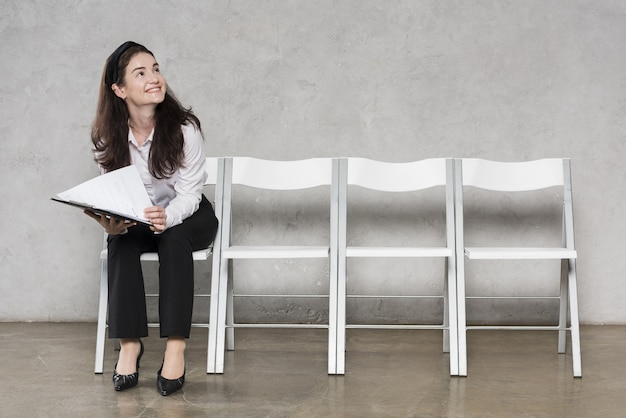 Front view of woman waiting for job interview with resume Premium Photo