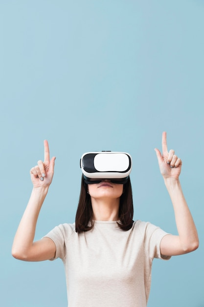Front view of woman wearing virtual reality headset and pointing up Premium Photo