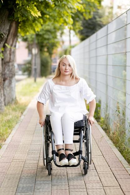 Vista frontale della donna in sedia a rotelle in città Foto Gratuite