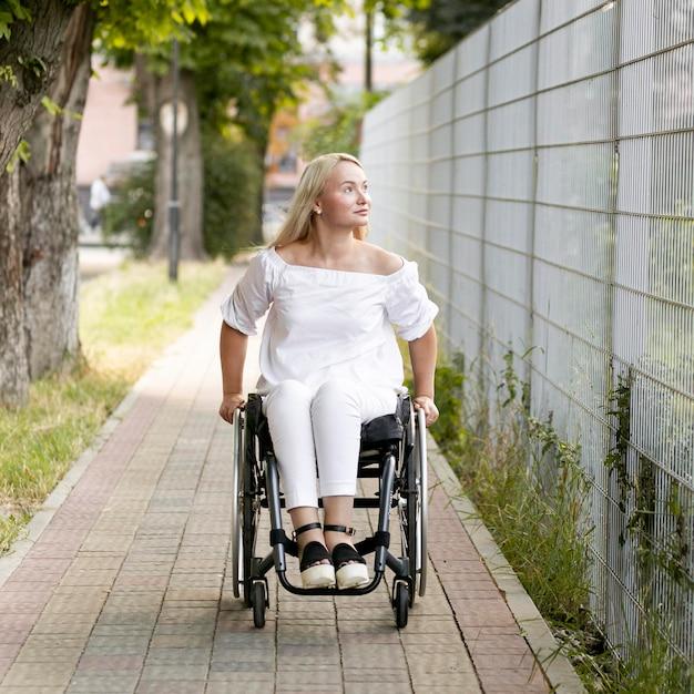 Vista frontale della donna in sedia a rotelle all'aperto Foto Gratuite