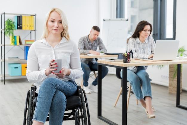 Vista frontale della donna in sedia a rotelle che posa sul lavoro mentre si tiene la tazza Foto Gratuite