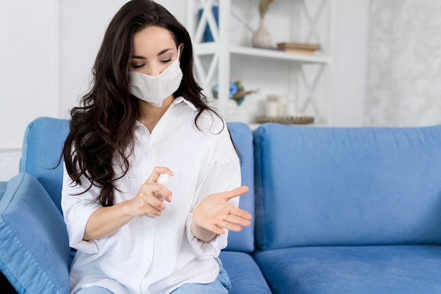 Front view of woman with face mask disinfecting her hands Premium Photo