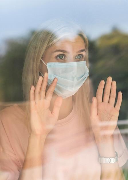 Vista frontale della donna con mascherina medica a casa toccando la finestra durante la pandemia Foto Gratuite