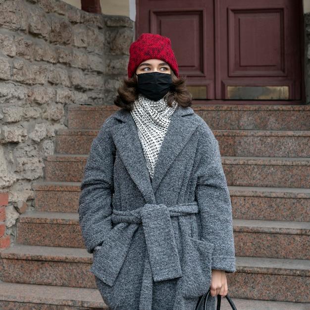 Vista frontale della donna con mascherina medica all'aperto Foto Gratuite