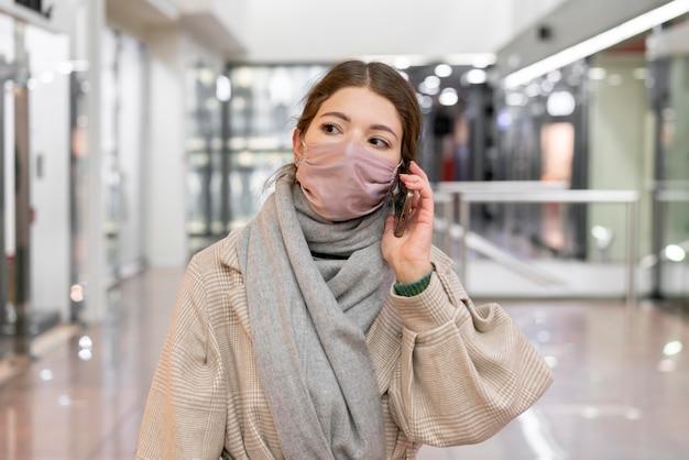 Vista frontale della donna con mascherina medica parlando al telefono Foto Gratuite