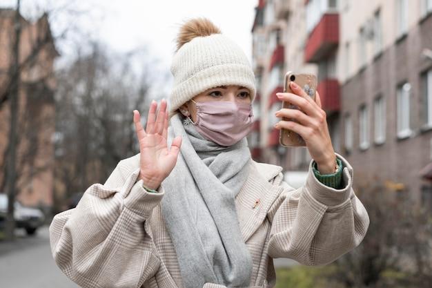 Vista frontale della donna con mascherina medica sventolando smartphone Foto Gratuite