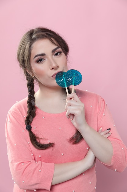 Front view of woman with ponytails posing with lollipops Free Photo