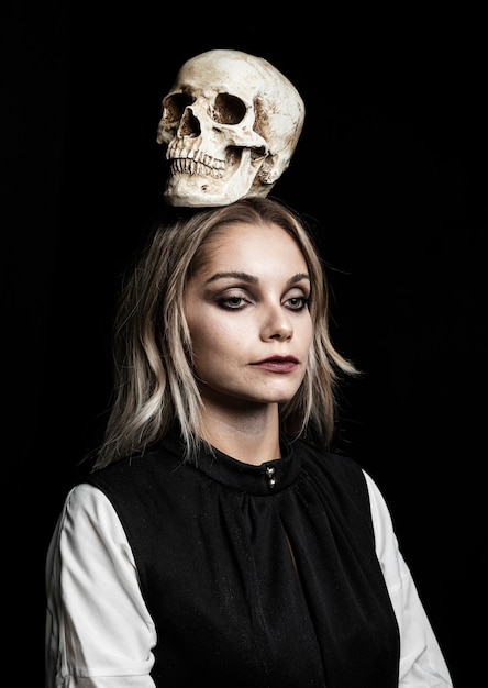 Front view of woman with skull on head Free Photo
