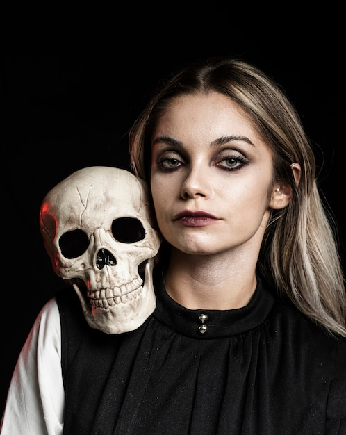 Front view of woman with skull on shoulder Free Photo