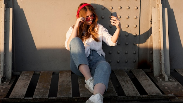 Front view of woman with sunglasses taking a selfie Free Photo