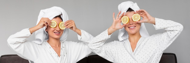 Front view of women in bathrobes and towels holding lemon slices over eyes Free Photo
