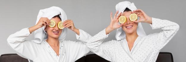 Vista frontale delle donne in accappatoi e asciugamani che tengono le fette di limone sopra gli occhi Foto Gratuite