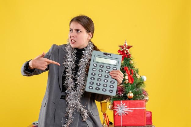 La ragazza si è chiesta la vista frontale che mostra il calcolatore che sta vicino all'albero di natale e al cocktail dei regali Foto Gratuite