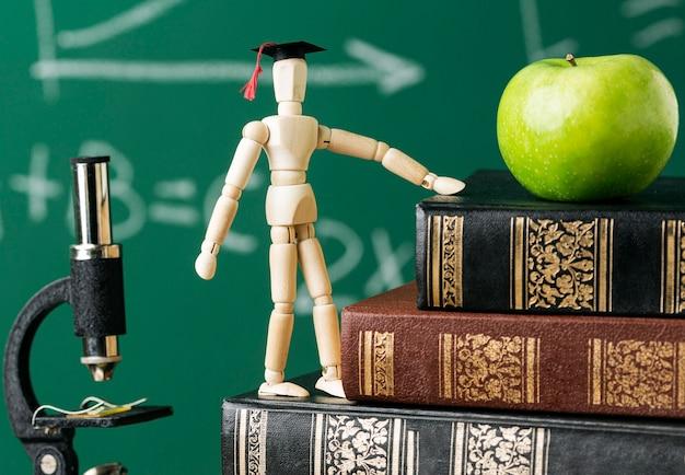 Vista frontale della statuina in legno con cappuccio accademico e mela Foto Gratuite