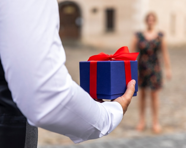 Front view wrapped gift held by man Free Photo