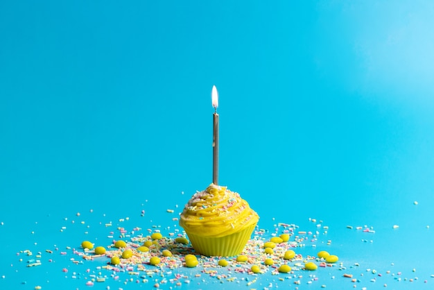 A front view yellow birthday cake with candle on blue Free Photo