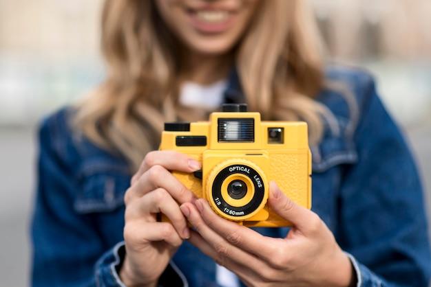 Macchina fotografica gialla di vista frontale e donna vaga Foto Gratuite