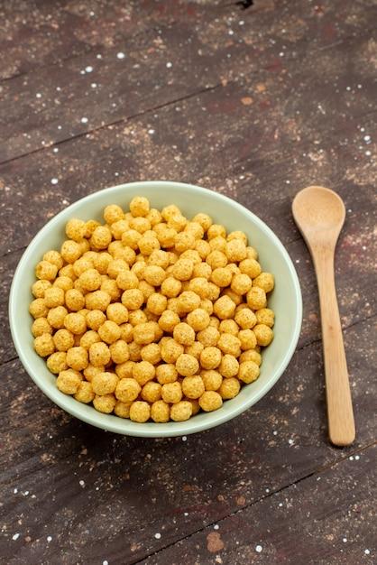 暗い木、朝食コーンフレークシリアル食品のプレート内の正面黄色の穀物 無料写真