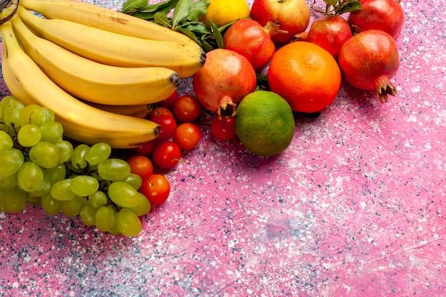 正面図ピンクの机の上にブドウとザクロと黄色の新鮮なバナナのおいしい果物 無料写真