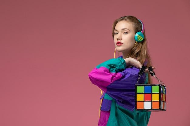 Giovane femmina attraente di vista frontale in cappotto colorato che ascolta la musica che tiene la borsa divertente sulla ragazza della femmina di colore del modello della parete rosa scuro Foto Gratuite