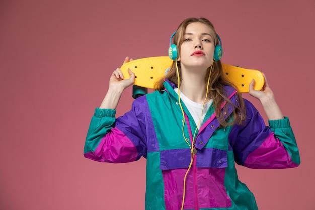 Vista frontale giovane femmina attraente in cappotto colorato ascoltando musica e tenendo lo skateboard e ascoltando musica sul muro rosa modello colore femmina giovane Foto Gratuite