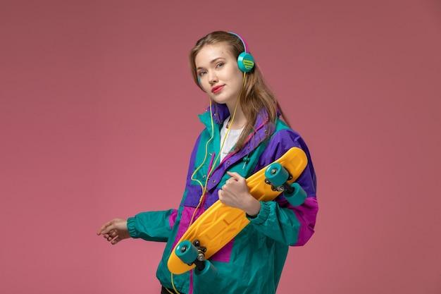 Giovane femmina attraente di vista frontale in cappotto colorato che ascolta la musica con lo skateboard sulla ragazza di colore rosa del modello della parete femminile Foto Gratuite