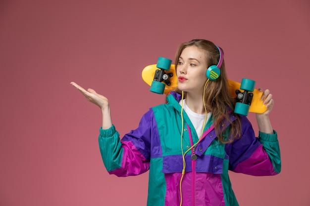 Vista frontale giovane femmina attraente in cappotto colorato in posa e ascolto di musica sul muro rosa modello colore femmina giovane Foto Gratuite