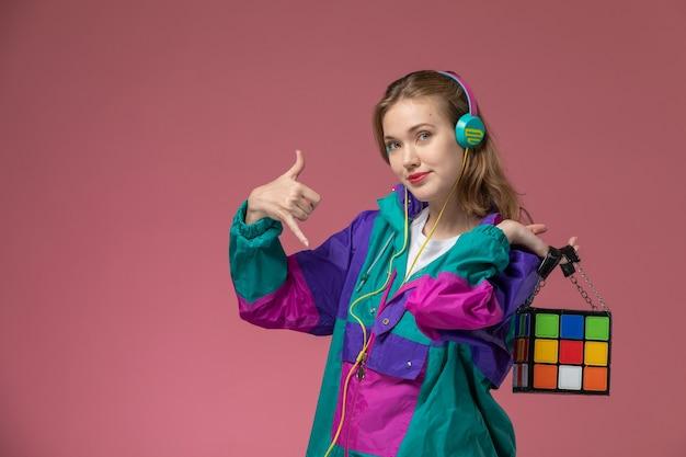 Vista frontale giovane femmina attraente in cappotto colorato sorridente ascoltando la musica sulla ragazza rosa modello scrivania colore femminile giovane Foto Gratuite