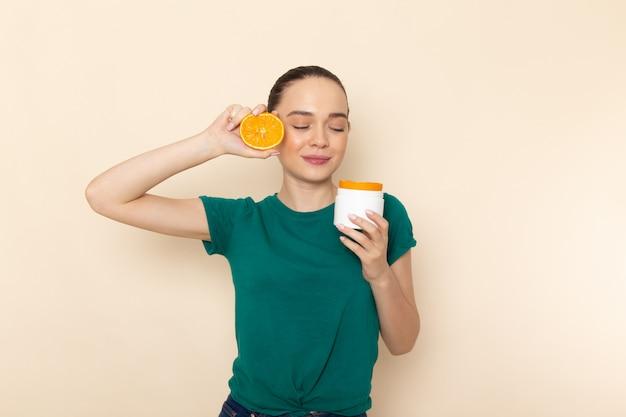 Giovane femmina attraente di vista frontale in camicia verde scuro che tiene arancio e latta sul beige Foto Gratuite