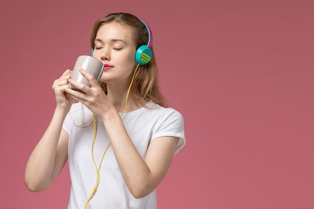 Vista frontale giovane donna attraente bere il tè e ascoltare musica sul muro rosa modello colore femmina giovane Foto Gratuite