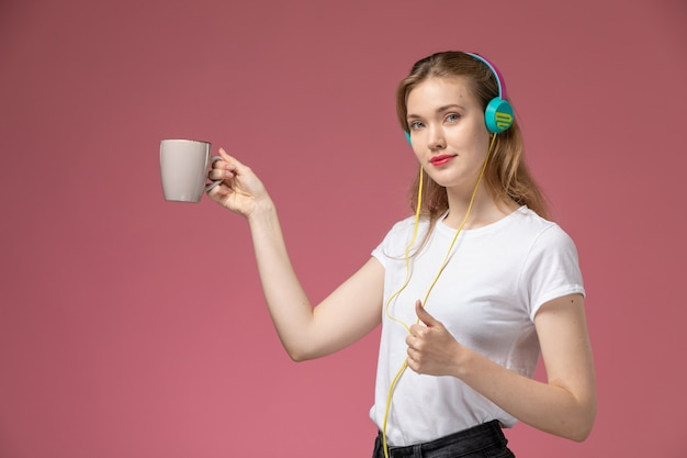 Vista frontale giovane femmina attraente che tiene tazza e ascolto di musica sulla parete rosa modello colore femmina giovane ragazza Foto Gratuite