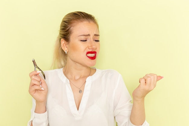 彼女の爪を固定し、緑の表面で怪我をしている白いシャツの正面図若い魅力的な女性 無料写真
