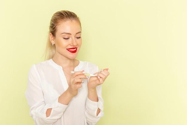 그녀의 손톱으로 작업하고 녹색 표면에 웃고 흰 셔츠에 전면보기 젊은 매력적인 여성 무료 사진