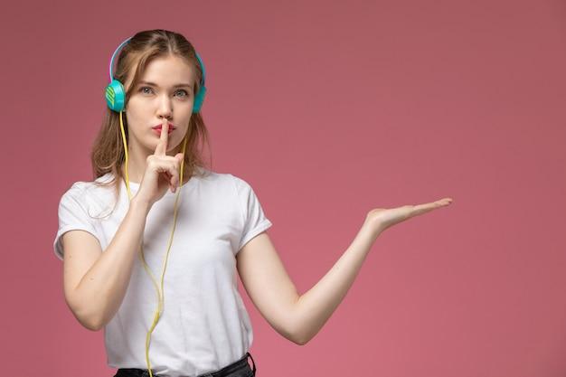 Giovane femmina attraente vista frontale che ascolta la musica e che mostra il segno di silenzio sulla ragazza della femmina di colore del modello della parete rosa Foto Gratuite