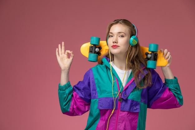Vista frontale giovane femmina attraente in t-shirt bianca cappotto colorato ascoltando musica tenendo skateboard su scrivania rosa modello femmina colore femmina giovane Foto Gratuite
