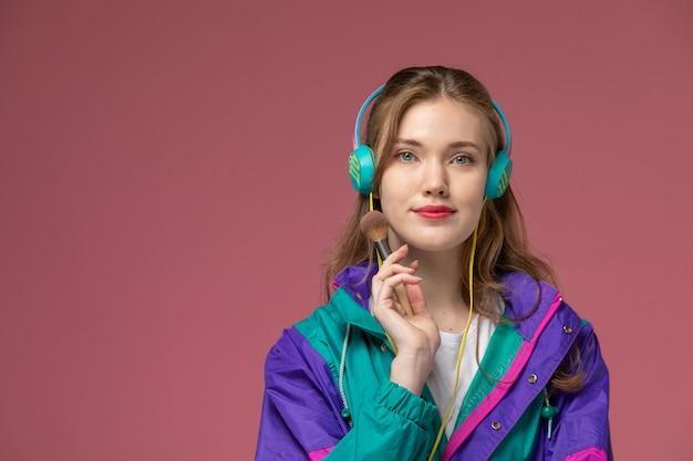 Vista frontale giovane femmina attraente in t-shirt bianca cappotto colorato ascoltando musica tramite auricolari sulla parete rosa modello femmina posa foto a colori Foto Gratuite