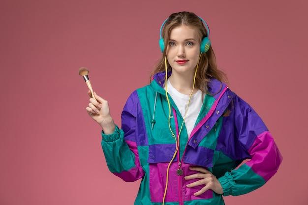 Vista frontale giovane femmina attraente in t-shirt bianca cappotto colorato ascoltando musica tramite auricolari sul muro rosa modello femmina posa colore Foto Gratuite
