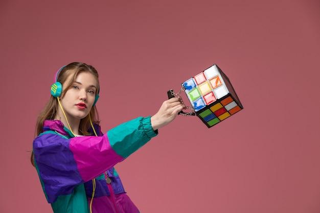 Giovane femmina attraente di vista frontale in cappotto colorato della maglietta bianca che posa ascoltando la borsa della tenuta di musica sul colore di posa femminile del modello della parete rosa Foto Gratuite