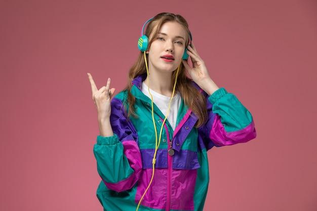 Vista frontale giovane femmina attraente in t-shirt bianca cappotto colorato in posa ascoltando musica sulla scrivania rosa modello femmina posa foto a colori Foto Gratuite