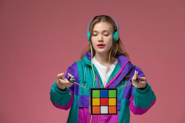 Vista frontale giovane femmina attraente in t-shirt bianca cappotto colorato in posa ascoltando musica sulla parete rosa modello femmina posa foto a colori Foto Gratuite