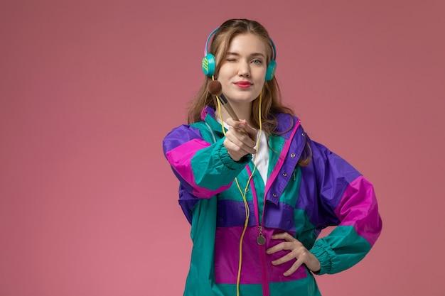 Vista frontale giovane femmina attraente in t-shirt bianca cappotto colorato in posa ascoltando musica con il sorriso sulla parete rosa modello femmina posa foto a colori Foto Gratuite