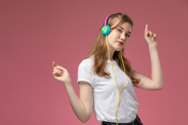 Giovane femmina attraente di vista frontale in maglietta bianca ballando e ascoltando musica sulla ragazza femminile di colore rosa scuro del modello della parete Foto Gratuite
