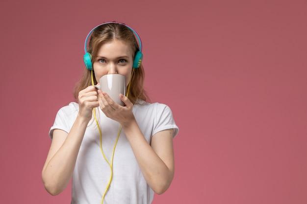 Vista frontale giovane femmina attraente in t-shirt bianca, bere il tè ascoltando musica sul muro rosa modello colore femmina giovane Foto Gratuite