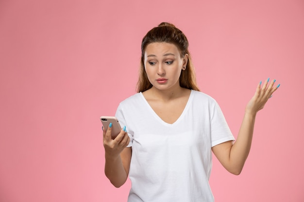 Front view young attractive female in white t-shirt using her phone on pink background Free Photo