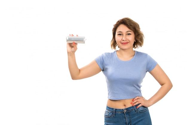 Una giovane signora attraente di vista frontale in maglietta grigia e blue jeans che tengono la latta d'argento che sorride sul bianco Foto Gratuite