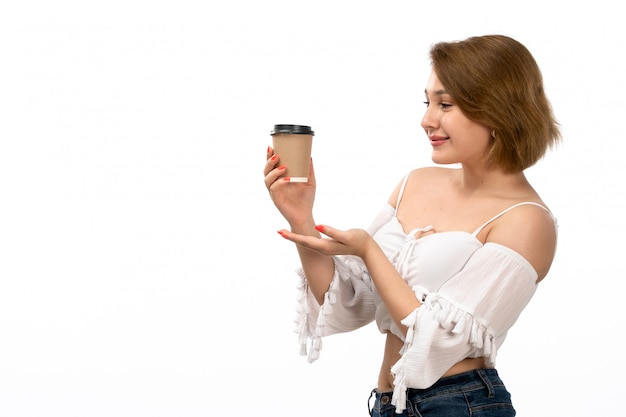 A front view young attractive lady in white shirt and blue jeans holding coffee cup delighted smiling on the white Free Photo