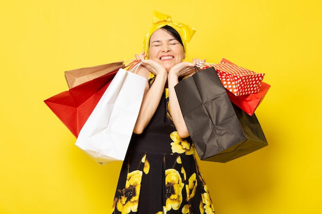 Una giovane signora attraente di vista frontale in vestito progettato fiore giallo-nero con la fasciatura gialla sulla testa che posa i pacchetti di acquisto della tenuta sul giallo Foto Gratuite