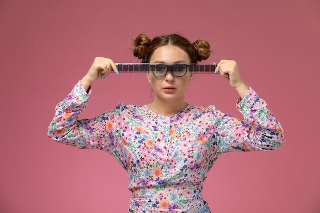 Vista frontale giovane bella femmina in fiore progettato camicia e blue jeans che tengono il vecchio nastro cinematografico sullo sfondo rosa Foto Gratuite