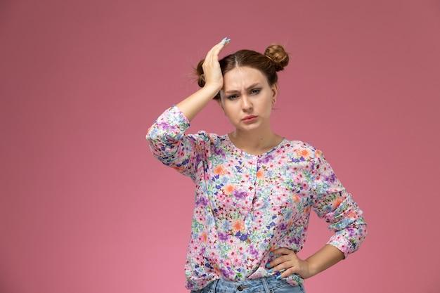 Вид спереди молодая красивая женщина в цветочной рубашке и синих джинсах с головной болью на розовом фоне Бесплатные Фотографии